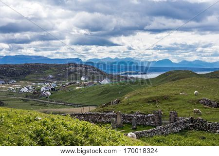 Assynt Peninsula Scotland - June 7 2012: The hamlet of Lochinver sits on the shore of Loch Inver an arm of the Atlantic Ocean. Blue-gray cloudscape and green pasture upfront. Horizon of mountains.