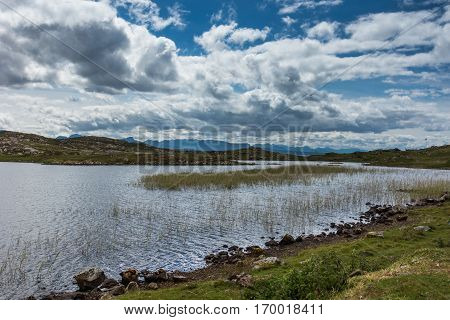 Assynt Peninsula Scotland - June 7 2012: Loch Sgeireach is a lake along B869. Here under blue sky with large white clouds. Reed in water some grass upfront. Horizon of mountains.