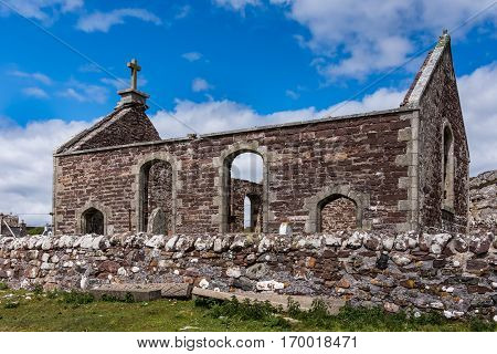 Assynt Peninsula Scotland - June 7 2012: Lateral view on roofless ruins of Parliamentary Church with small cemetery and historic tomb stones. Brown-reddish stones. Blue sky with white clouds. Green grass.