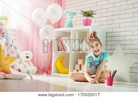 Happy child plays. Little child girl draws with colored pencils indoors. Funny lovely child having fun in children room.