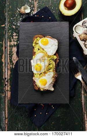 Fried egg sandwich: quail eggs, avocado and cheese on whole wheat bread