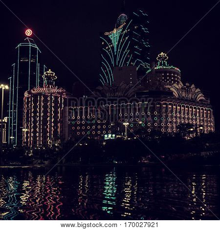 Macao - October 2016: Night view with glowing Casino Lisboa and reflection in water.