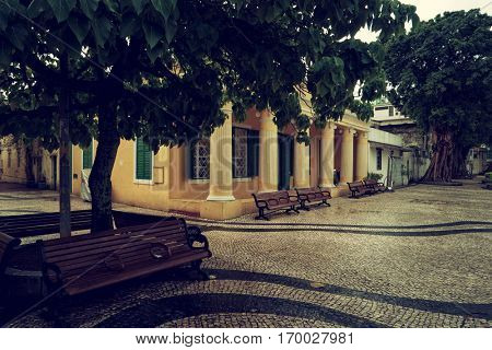 Macao - October 2016: View of tree and bench with Coloane Library in background.