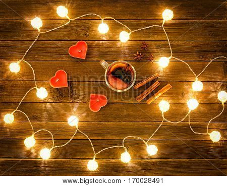 Top view of mulled wine with spices candles in the shape of a heart cinnamon sticks star anise on a wooden table. Garland of lanterns.