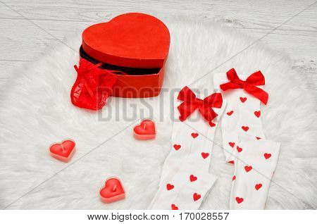 Fashion concept. Red box heart shaped with lace lingerie white stockings with bows candles in the shape of a heart on a white fur.
