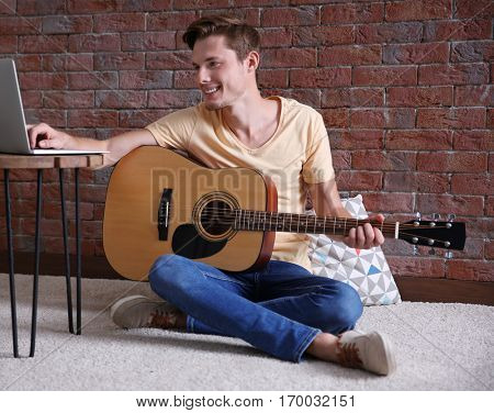 Young man playing guitar and composing song in room