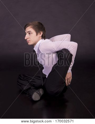 Extraordinary gymnast on a black background. The man with no bones. Studio photography of circus performers..