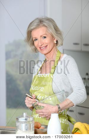 Closeup of smiling senior woman baking in kitchen