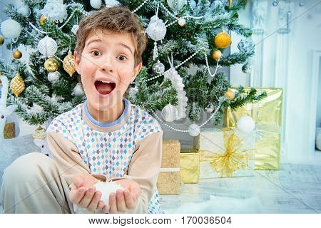 Happy nine year old boy in pajama sitting under the Christmas tree with snow in his palms. Christmas concept. Gifts and miracles.