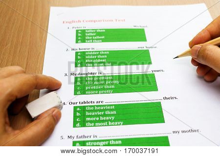 multiple choice english exam with hand on table
