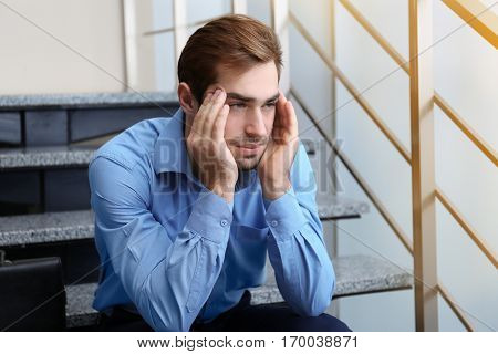Tired office worker sitting on stairs indoors