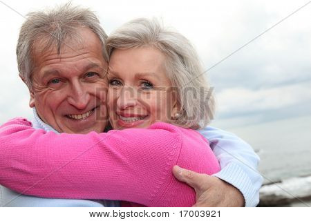 Happy senior couple embracing each other by the sea