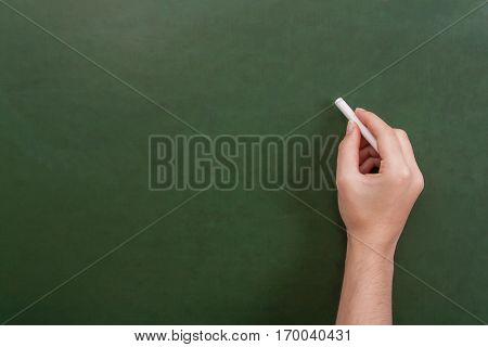 Close up of a teacher or student hand holding a chalk stick about to write on a blank green chalkboard with copyspace