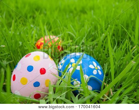 Hand painted Easter eggs hidden on the grass ready for the easter egg hunt traditional play game