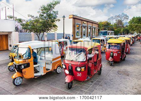 OAXACA, MEXICO- DEC 10, 2015:  Taxi tuk-tuk column at the street of Oaxaca on Dec 10, 2015, Mexico.