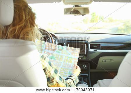 Female driver searching direction on map