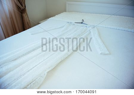 Wedding dress with hanger laying on the bed.