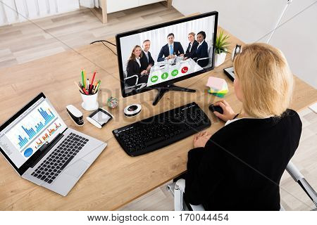 High Angle View Of A Businesswoman Videoconferencing With Her Colleagues On Desktop Computer
