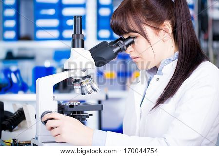 Young scientist studying new substance or virus in microscope. 
