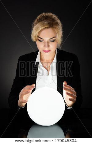 Young Businesswoman Looking Into The Future In A Crystal Ball On Black Background. Fortune Teller Predicting Future