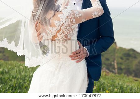 Groom kissing the bride in a wedding dress an oceanfront close-up