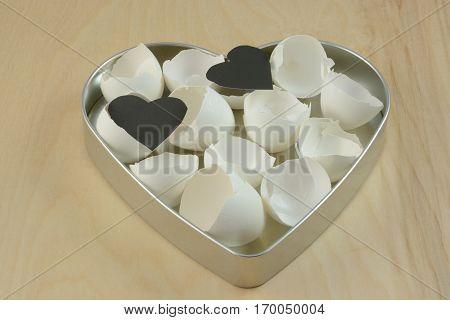 Anti-valentine of broken fragile eggshells and two black hearts in bigger metal heart