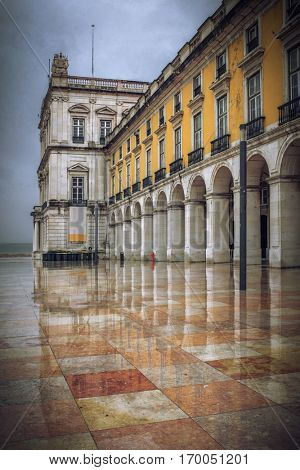 Building of Terreiro do Paco in Lisbon and reflection in the ground in a wet rainy day