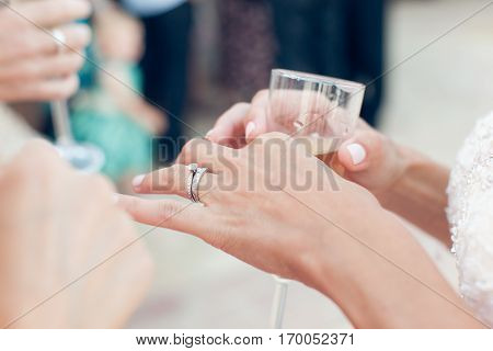 Bride with wedding ring holds a glass of champagne close-up
