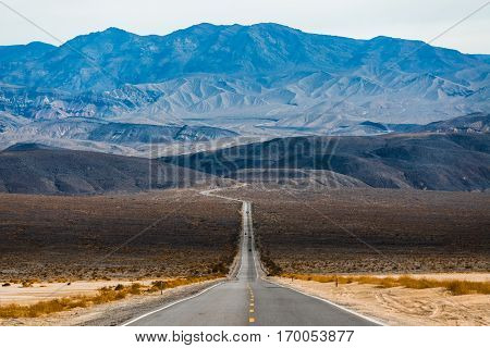 Road in the Death Valley National Park with mountains on the horizon. USA
