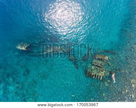Aerial shot of the Japanese ship wreck with people snorkeling over it. Bali, Indonesia