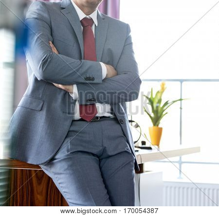 Portrait of mature businessman with arms crossed leaning on desk in office