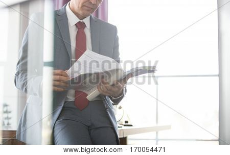 Mature businessman reading book while leaning on desk in office