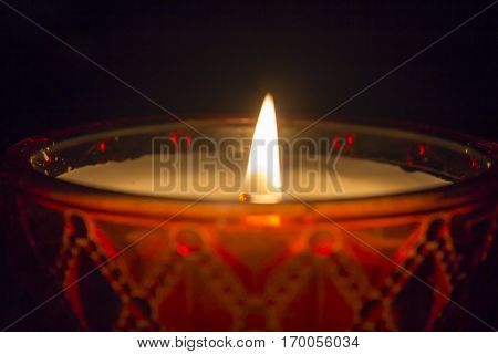 One candle flame at night closeup - isolated, macro.