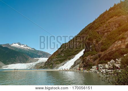 Glacier and waterfall tour in Alaska. People on holiday vacation in Mendenhall glacier alaska