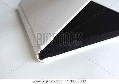 Big photobook lay on wooden table white with black pages.