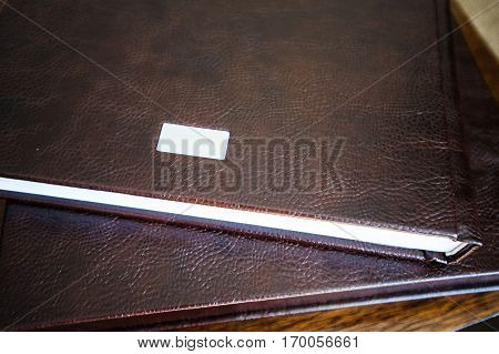 Big photobook lay on wooden table color dark brown with bright pages.