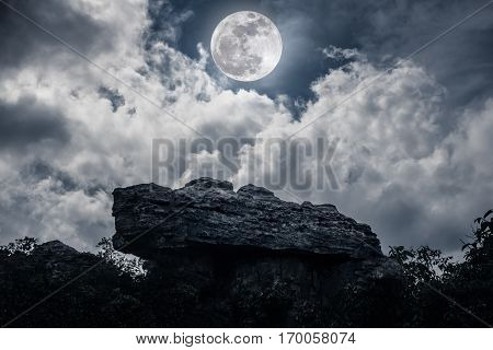 Boulder Against Sky With Clouds And Beautiful Full Moon At Night. Outdoors.