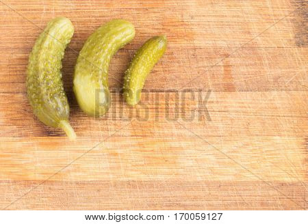 Homemade Pickled Gherkins or Cucumbers on Wood Cutting Board