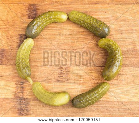 Round Frame of Homemade Pickled Gherkins with Copy Space. Marinated Cucumbers Over Rustic Wooden Background