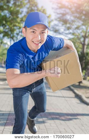 deliveryman hold box and smile to you asian