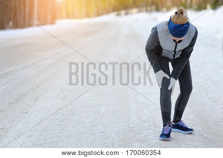 Injuries - Sports Running Knee Injury On Woman. Winter Marathon.