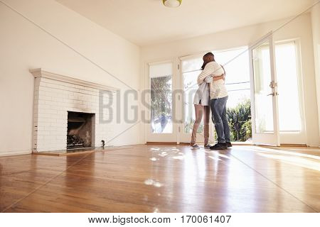 Excited Couple Hugging In New Home On Moving Day