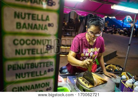 PATONG BEACH THAILAND - 9 FEBRUARY 2017: Nightlife in Thailand. Street food. A woman prepares a pancake with banana and sweets in the street.
