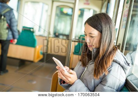 Woman using cellphone inside train compartment at Japan