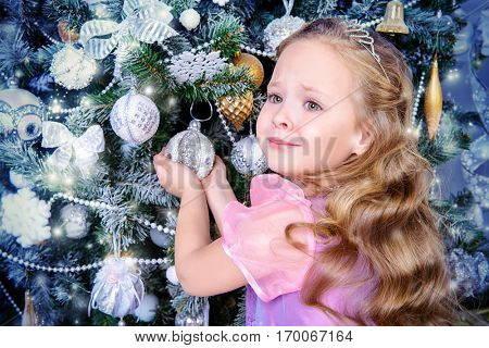 Happy little girl in a beautiful dress decorates the Christmas tree. Merry Christmas.
