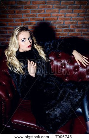 Beautiful blonde woman wearing mink fur coat posing in luxurious interior. Fashion, beauty. Winter collection.