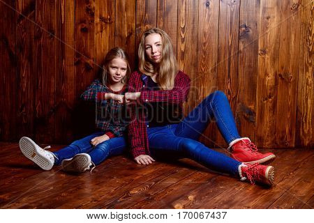 Modern generation. Two cute girls, older and younger sister sitting together on a floor.