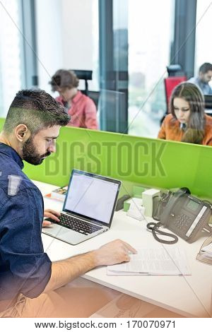 Businessman reading book while using laptop in office