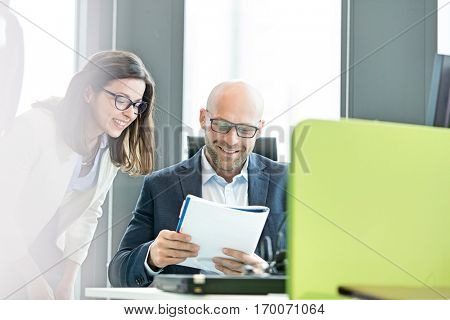 Smiling businesswoman and businessman reading book at office