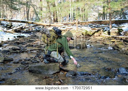 Man In Forest Drinking From A Mountain Stream